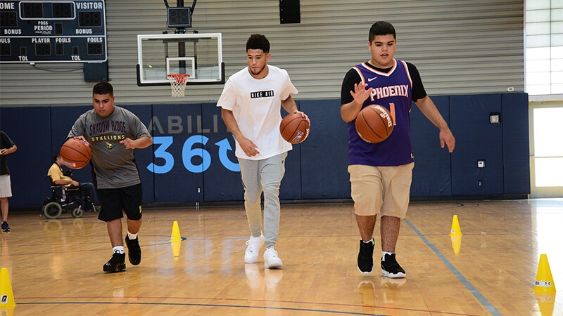 Booker joins Special Olympics athletes in a dribbling drill on the court between small yellow cones.
