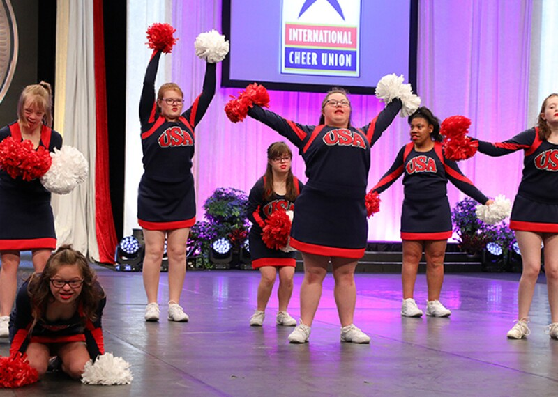 7 cheerleaders performing on stage in red and blue outfits with USA across the front.