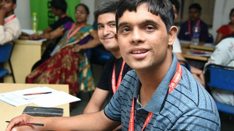 A teenage boy sits at a desk with his peer, smiling at the camera. He holds a pen in his hand, touching a notebook on his desk. There room is full of youth and adults at desks in the background.