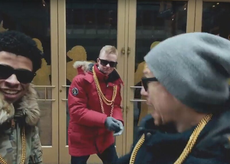 Three men in winter coats with gold chains around their necks and sunglasses on standing in front of a group of doors.