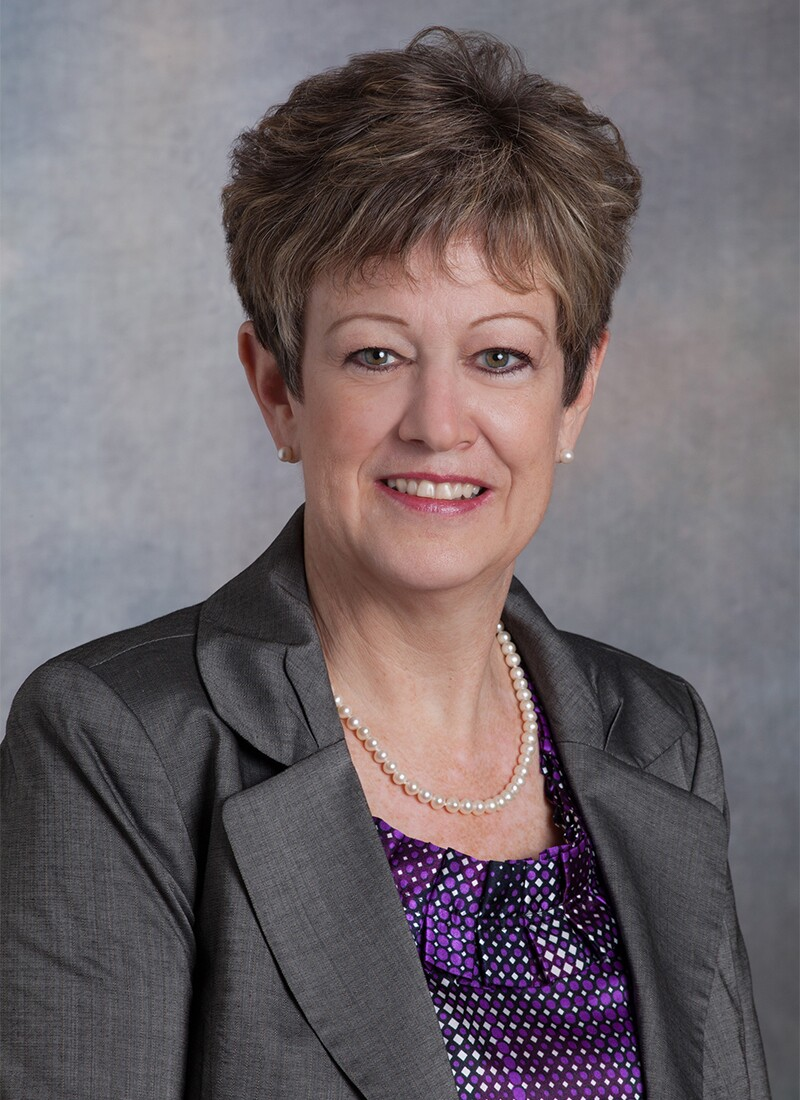 Mary Rosendahl sitting for a professional photo in front of a gray cloudy background. She has short light brown and gray hair, charcoal suit jacket, purple and white diamond-pattern top, and a simple pearl necklace.