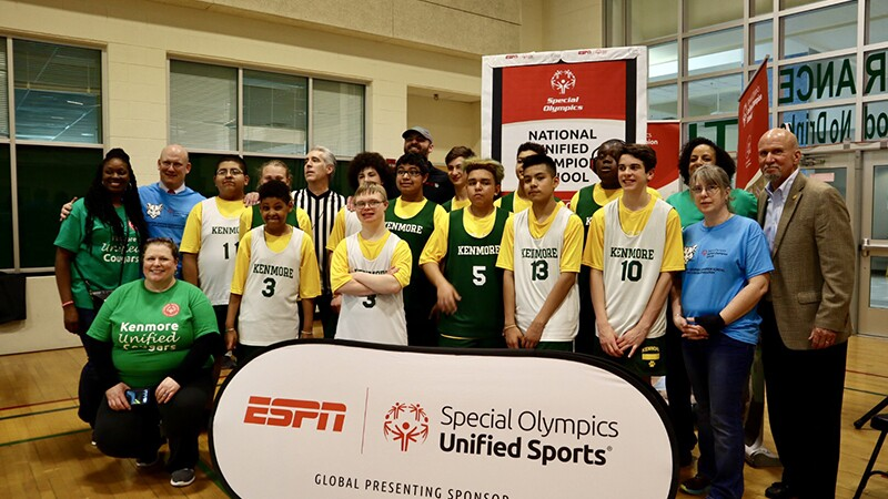 Group photo of a unified athletes team standing in a group with Special Olympics Unified Sports signage in front and behind them.
