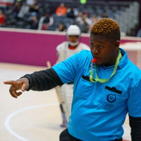 Jimmy Masina reffing a floor ball game; a player can be seen in the background.