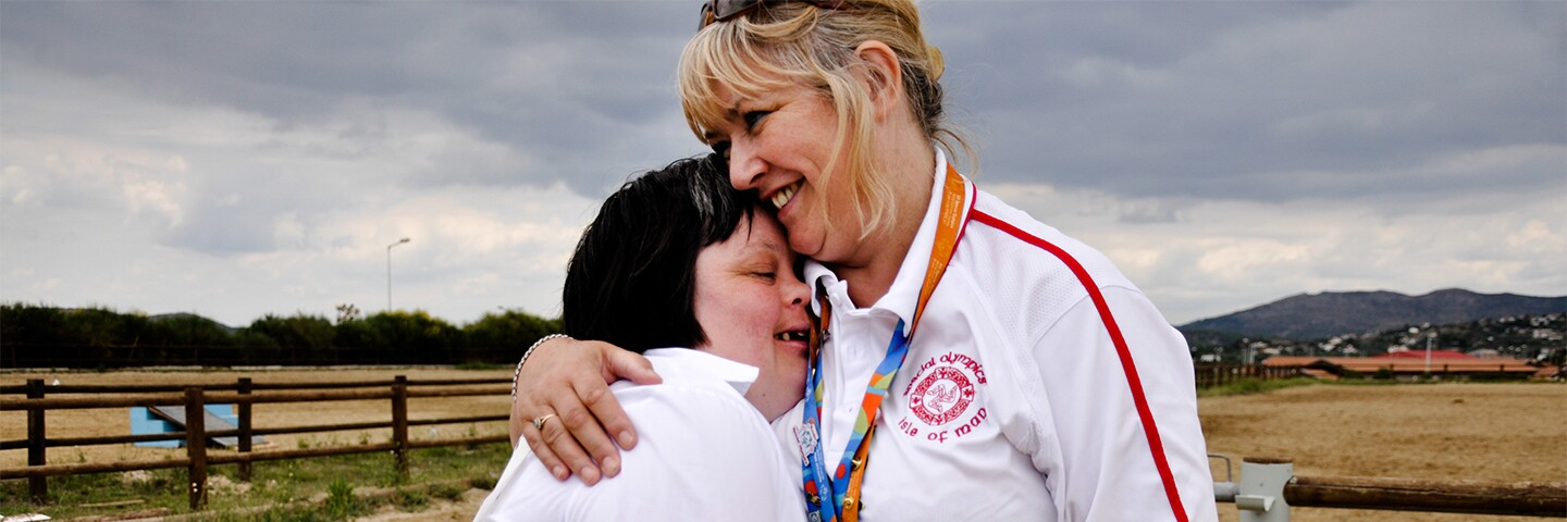 Volunteer hugging an athlete outside with a field in the background.
