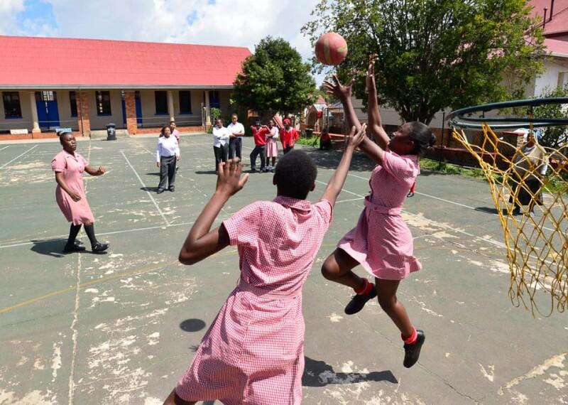 Female athletes practice netball on the court.