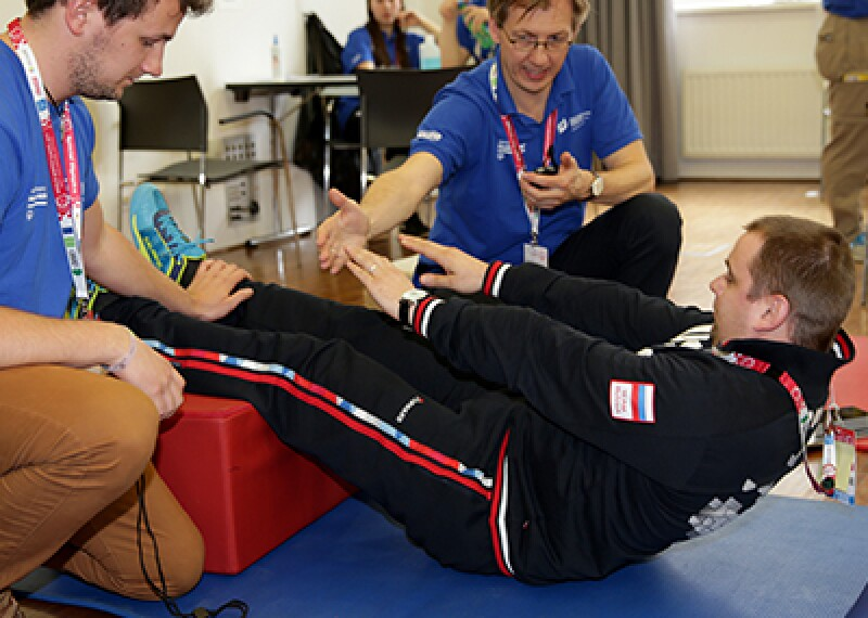athlete laying on his back with his legs elevated reaching to touch his toes; two volunteers observe and encourage him.