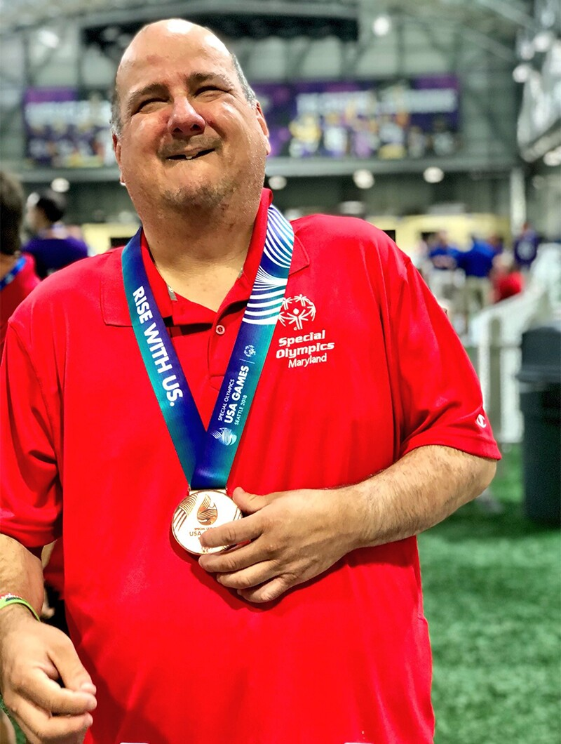 Ben after winning Bronze at the 2018 Special Olympics USA Games in Seattle. He is in standing inside the facility with patrons and athletes in the background; Ben is wearing a red Special Olympics polo and has a Bronze medal around his neck.