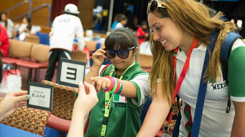 Special Olympics athlete has her eyes tested and points to an eye test card.