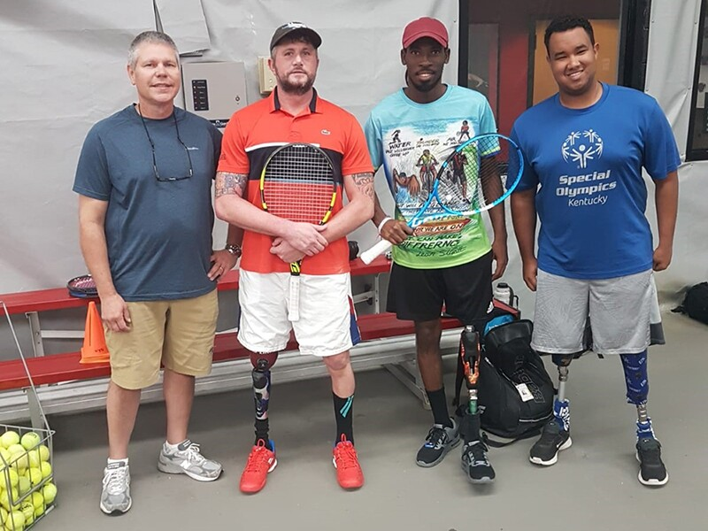 From Left to right: Wayne Luckett, Jeff Bourns, Dionte and Morgan Turner causally standing and smiling for the photo. Jeff and Dionte are holding rackets.