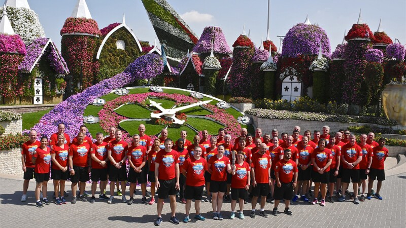Members of the LETR Final Leg team pose in front of the flowers in the Dubai Miracle Garden.