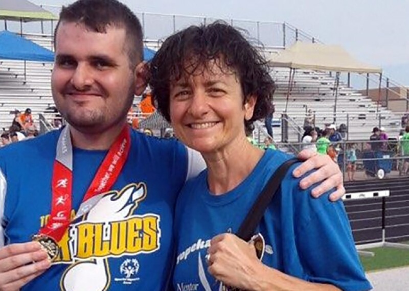 Special Olympics Kansas athlete Cort Huffman is pictured smiling and displaying his medal after competing at a Special Olympics event.