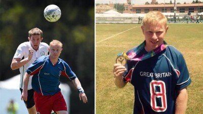 A man runs at the soccer ball. He is wearing a blue and red uniform. A player from a different team runs after the ball behind him. | A Special Olympics Great Britain stands on a football field showcasing his gold medal.