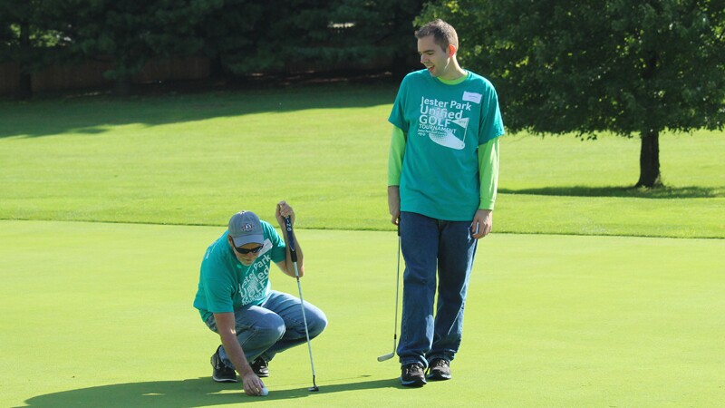 Tyler Leech on the green playing golf with another player.