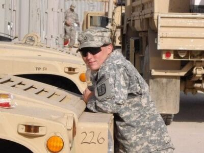 Monica Klock leans on a military vehicle while in Iraq.