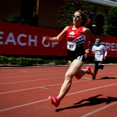 Female Canadian runner running on a track