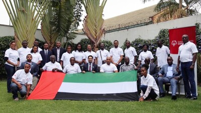 Special Olympics leaders and representatives in a group photo in Africa. A Unified Sports banners is in the background, a country flag is in the foreground.