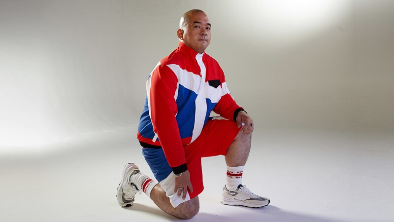 Alfred Ha kneeling down in a red white and blue jump suit with shorts.