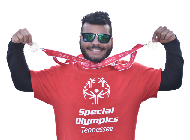 smiling athlete in red Special Olympics t-shirt holds up two medals