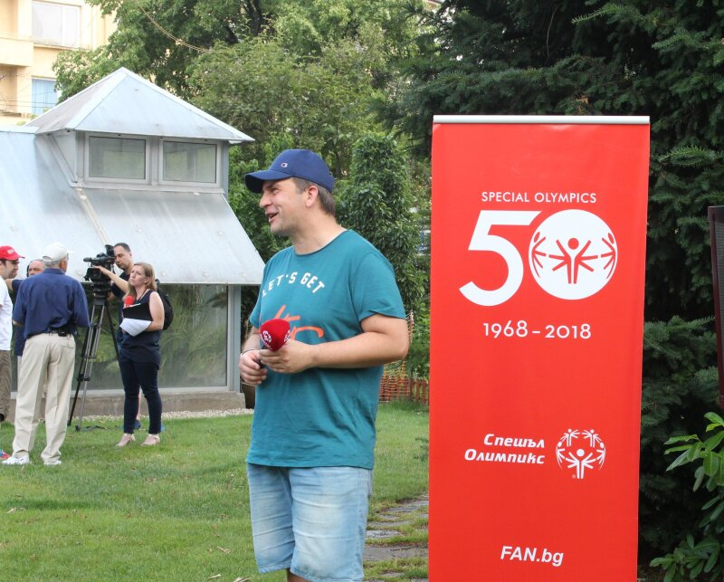 A man wearing a baseball hat, a turquoise t-shirt and jeans shorts stands in front of a red Special Olympics 50 pull-up banner holding a red microphone in a garden setting.