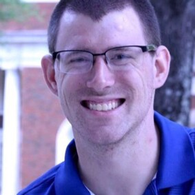 RJ smiling for a photo; he has on glasses and a blue polo.