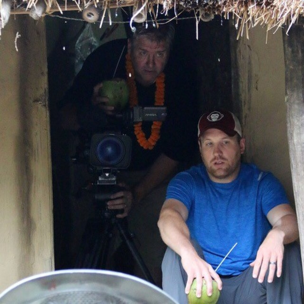 The videographer (holding his camera) is standing behind a seated man in a blue shirt holing a coconut. Both are in a small hut enclosure.