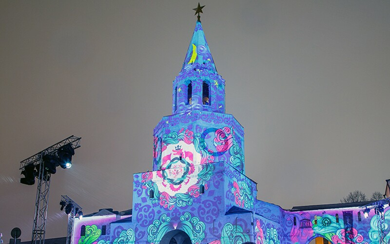 A large white building with a steeple with a star at the top has the Kazan logo of white, pink, and teal dragons and swirls projected onto it, at nighttime.