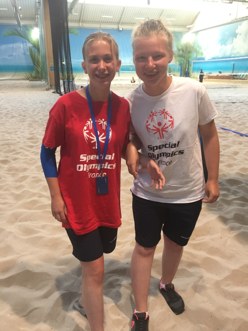 Two blonde girls in Special Olympics t-shirts stand side by side smiling at the camera standing on sand with a beach volleyball net in the background.