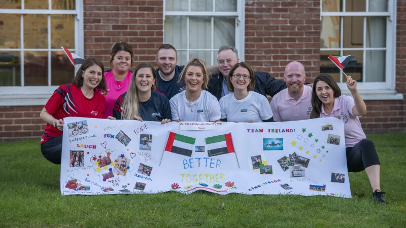 A group of volunteers crouch on the grass in from of a building. They are smiling and holding a banner that reads 'Better Together' with decorations and two flags.
