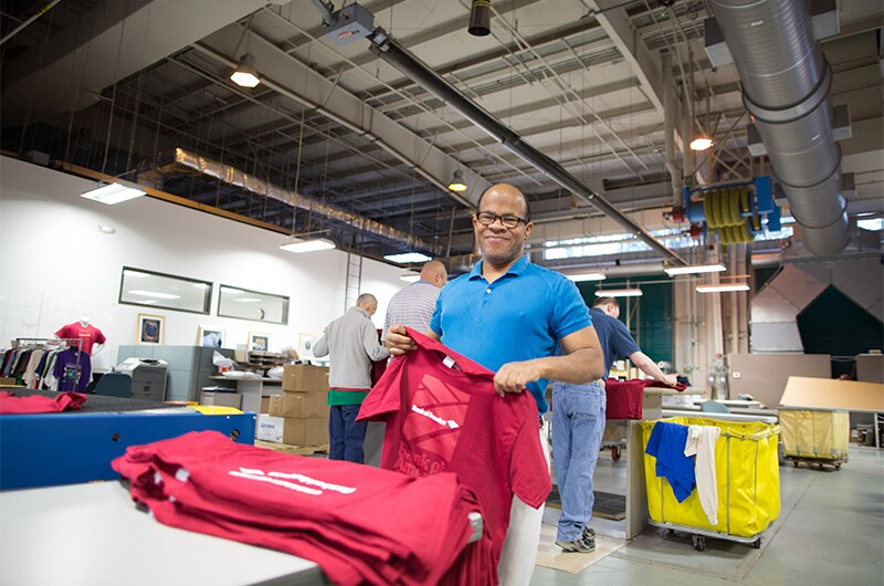Bank of America Support Services print shop produces all in house t-shirts. Employee in a blue polo holding a red t-shirt from a stack of red t-shirts in front of him.