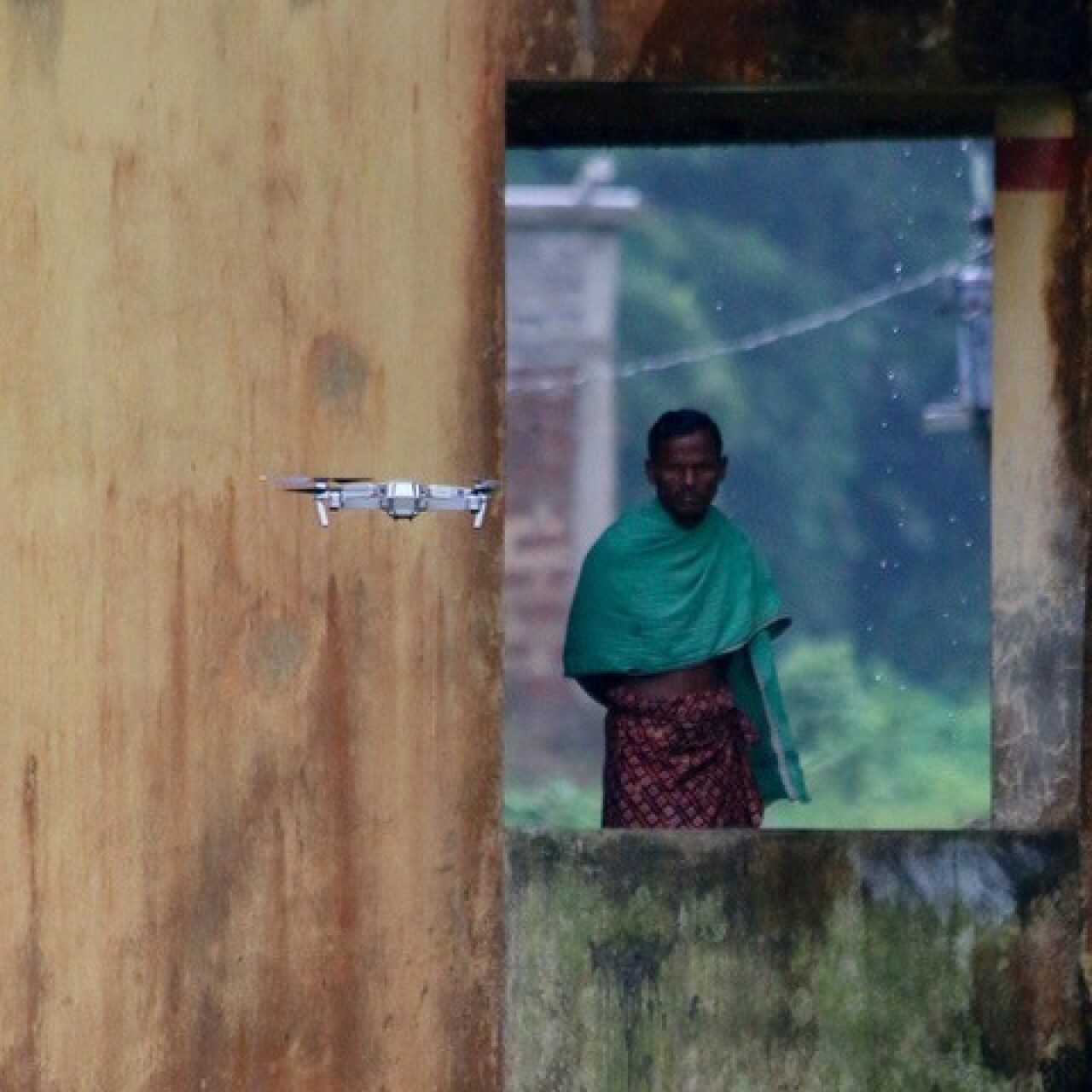 a small drone is flying in the foreground. There is a small building with an opening and a man is looking at the photographer; rain is falling in the background.