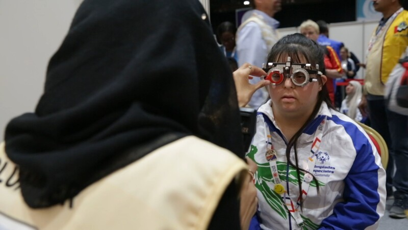 An athlete with an apparatus over her eyes receiving a vision screening from a health volunteer.