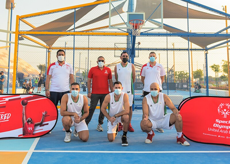 Special Olympics United Arab Emirates athletes pose on basketball court.