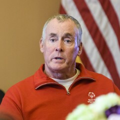 John C. McGinley in a red zip up Special Olympics sweater with the American flag in the background.