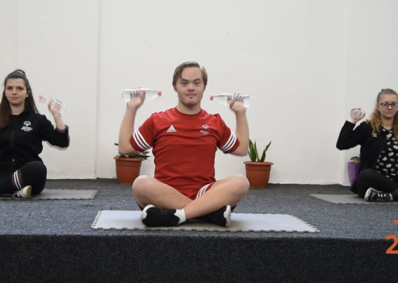 Three athletes sitting on a platform working out.