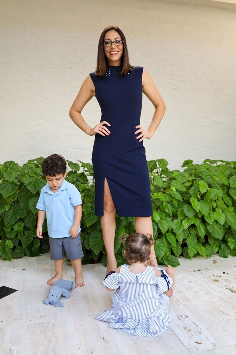 Justine standing outside with two young children.