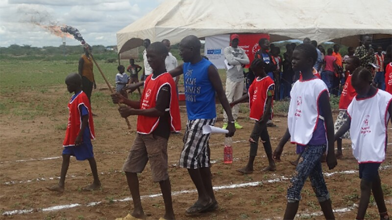 A group of youth in Special Olympics Kenya jerseys walks across a dirt track in front of a crowd. One youth carries a lit torch.