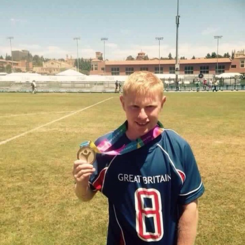 A Special Olympics Great Britain stands on a football field showcasing his gold medal.