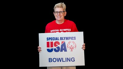 Cindy Schopper holding a sign that reads: Special Olympics USA Bowling