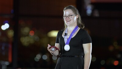 Melissa on stage with a medal draped around her neck speaking at SOMA's 50th Anniversary in 2018.
