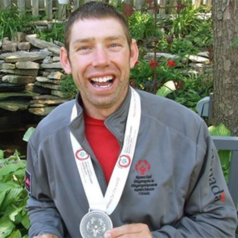 Stephen Graham smiling with a Special Olympics track suite on and a silver medal around his neck.