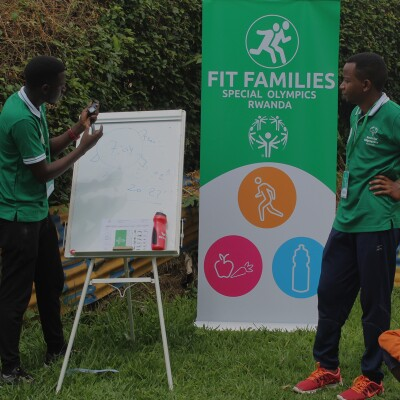 One man drawing on a white board and another standing next to a pull up banner that reads, Fit Families Special Olympics Rwanda.