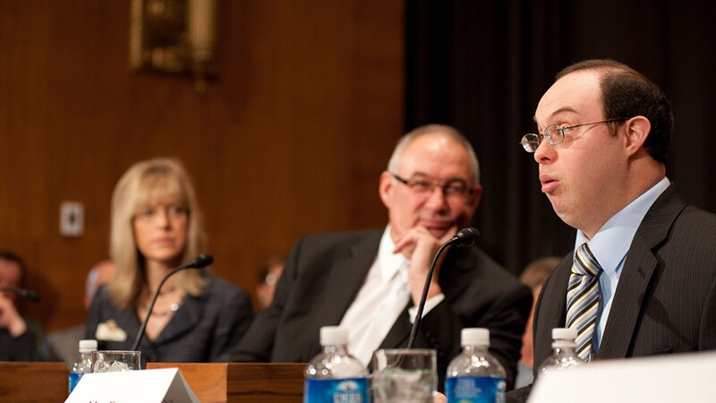 David Egan testifying, speaking into a microphone. Two officials are to his left, a male and female both dressed in business suits.