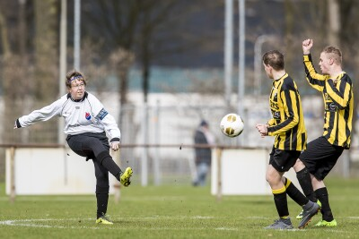 Female football/soccer player kicks the ball towards two male players on a football pitch.