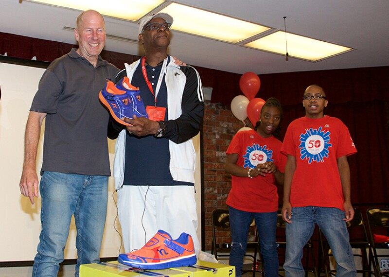 George Piece (on the left) and Bob Beamon (on the right) speak at the Southside Occupational Academy High School in Chicago. Two athletes are in the background watching George and Bob present the shoes to an audience.