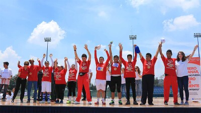 A group of students stand on stage celebrating with their hands up.