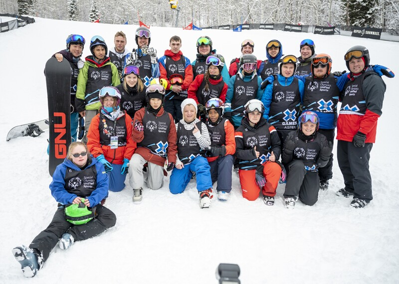 22 people pose in a group photo on the slopes after competing. All of them are wearing brightly colored snow clothes, goggles, and helmets. One of them holds a snowboard.