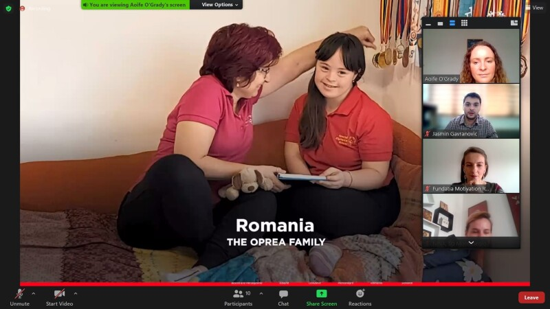 A screenshot of a Zoom meeting featuring, in the main screen, two woman sitting on a bed with the caption Romania, The Oprea Family as well as four small squares for other attendees along the side of the screen.