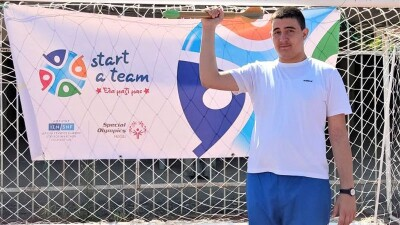 Young man standing in front of a Special Olympics flag, holding a javelin