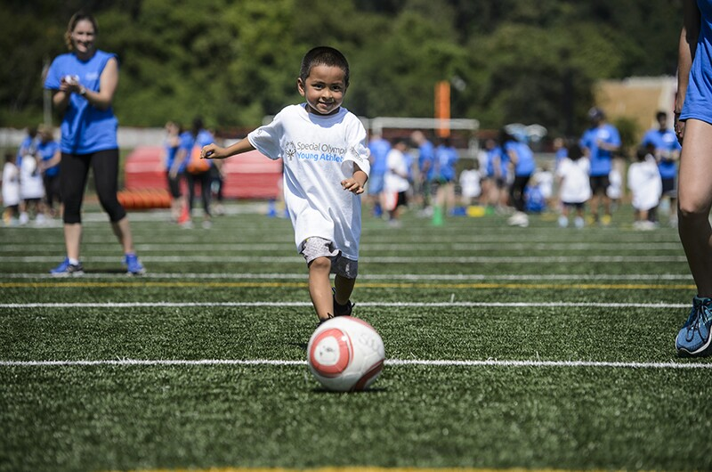 A young athlete in the center smiles at the camera as he prepares to kick a soccer ball on a soccer field while two volunteers watch.