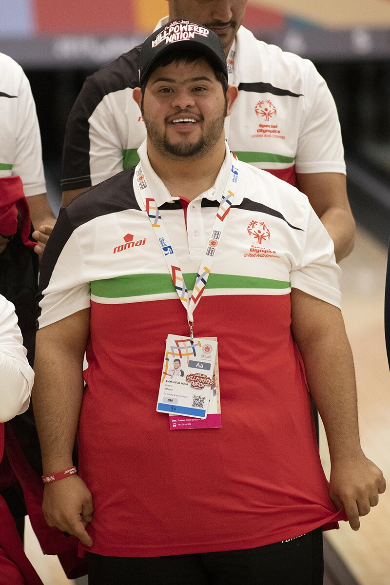 Saleh Al Marri standing for this photo. He has on a red white and green Special Olympics United Arab Emirates polo.